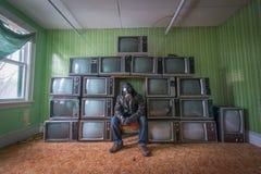 L'explorateur urbain s'assied parmi de vieilles télévisions dans une salle abandonnée Images stock