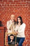L'exposition de père et de mère chut, et fils montre chut de la maison improvisée dans le studio sur le fond du mur de briques Co Images stock