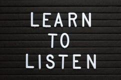 L'expression apprennent à écouter dans les lettres blanches sur un panneau d'affichage photographie stock libre de droits