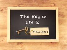 L'expression la clé à la vie est bonheur écrit sur le tableau noir Image stock