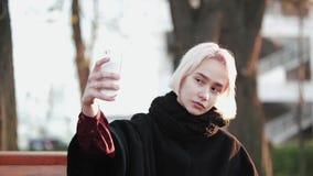 L'extérieur blond de fille tient un smartphone et le café font à un selfie flashes sérieux par de beaux de visage Sun banque de vidéos