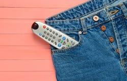 L'extérieur de TV dans des jeans empochent sur un fond en bois rose Images libres de droits