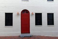 L'extérieur du bâtiment avec le blanc a peint la brique, la porte rouge lumineuse, et les lanternes de cuivre Images libres de droits
