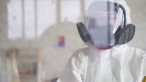L'exterminateur dans des vêtements de protection et un protecteur effectue la préparation de surface clips vidéos