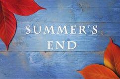 L'extrémité de l'été des textes écrite sur le fond en bois et bleu avec les feuilles d'automne dans les coins Photographie stock