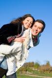L'extrémité de sourire de jeunes couples d'amour volent sous le ciel bleu Photos libres de droits