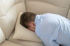 L?gengesicht des deprimierten Jugendlichen unten auf Sofa stockfotografie