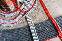 L?gga av elektricitetskablar, n?tverk, uppv?rmning Korrugerade linjer p? betong royaltyfri bild