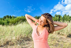 L girl in pink dress on seacoast Royalty Free Stock Image