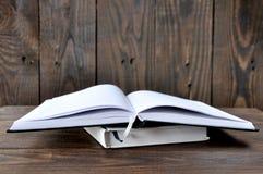 L?gner f?r en ?ppen bok eller anteckningsbokp? en tr?tabell arkivfoto