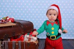 L?gner f?r pappers- pengar p? svart kol En liten pojkeuppklädd som en älva står i julpynt royaltyfri foto