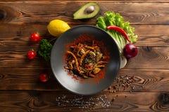 L?gumes de wok avec des ?pices dans un plat noir image stock