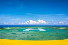 L'héliport vide de plate-forme pétrolière avec peu opacifient et ciel bleu Images libres de droits