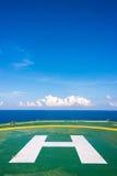 L'héliport vide de plate-forme pétrolière avec peu opacifient et ciel bleu Photographie stock libre de droits