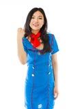 L'hôtesse d'air asiatique poinçonne le poing dans l'air d'isolement sur le fond blanc photos libres de droits