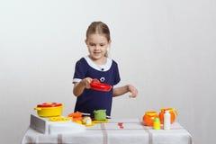 L'hôtesse de fille garde la casserole avec le poulet Image stock