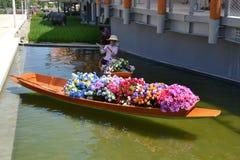 L'h?tesse du pavillon de la Tha?lande de l'EXPO Milan 2015 s'assied dans un bateau en bois tha?landais traditionnel rempli de tas photos stock