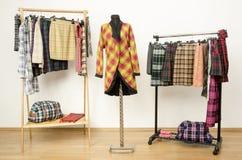 L'habillage du cabinet avec des vêtements de plaid a arrangé sur des cintres et un manteau sur un mannequin Photo libre de droits