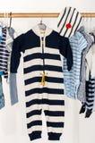 L'habillage du cabinet avec le bébé a barré des vêtements disposés sur des cintres photos libres de droits