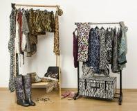 L'habillage du cabinet avec les vêtements animaux d'impression a arrangé sur des cintres. image libre de droits