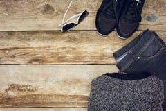 L'habillement et les accessoires des femmes : chandail, jeans, espadrilles et lunettes de soleil gris Photos libres de droits