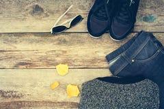 L'habillement et les accessoires des femmes : chandail, jeans, espadrilles, lunettes de soleil et feuilles gris de jaune Photo stock