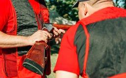L'habillement spécial de deux chasseurs considèrent le fusil de chasse photos stock