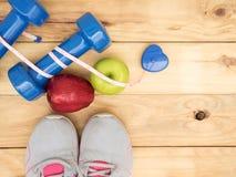L'haltère et la mesure et les chaussures bleues folâtrent avec la pomme sur b en bois Photographie stock libre de droits