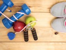 L'haltère et la mesure et les chaussures bleues folâtrent avec la pomme sur b en bois Images stock