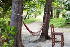 L'hamac lumineux de Bourgogne accroche entre deux arbres avec une chaise se tenant tout près Image stock