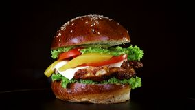 L'hamburger avec un grand morceau de viande, les verts et le fromage tournent sur un conseil en bois sur le fond noir banque de vidéos