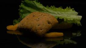 L'hamburger cade nell'azione lenta sulla tavola video d archivio