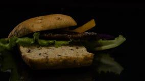 L'hamburger cade nell'azione lenta sulla tavola stock footage