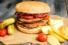 L'hamburger con la cotoletta e gli ortaggi freschi del manzo ha fritto la patata su fondo di legno immagini stock libere da diritti