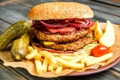 L'hamburger con la cotoletta e gli ortaggi freschi del manzo ha fritto la patata su fondo di legno fotografia stock libera da diritti