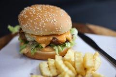 L'hamburger con le patate fritte è servito su un piatto di legno immagini stock libere da diritti