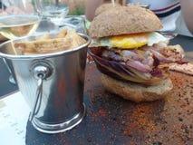 L'hamburger dans un petit pain complet a servi avec des fritures image libre de droits