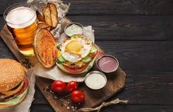 L'hamburger e le patate sono servito con la birra al ristorante fotografia stock