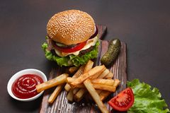 L'hamburger fait maison avec des ingr?dients ?toffent, les tomates, la laitue, le fromage, l'oignon, les concombres et les pommes photo libre de droits
