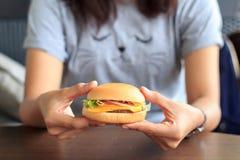 L'hamburger nella mano della giovane donna, tenente nella donna passa l'hamburger degli alimenti a rapida preparazione, hamburger Immagine Stock