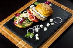 L'hamburger ouvert se trouve sur l'ardoise tile-2 Image stock