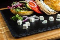 L'hamburger ouvert se trouve sur la tuile d'ardoise Photographie stock libre de droits