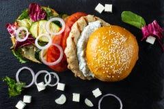 L'hamburger ouvert se trouve sur la tuile d'ardoise Photo stock