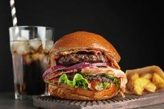 L'hamburger saporito con bacon e le patate fritte è servito fotografie stock