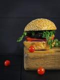 L'hamburger savoureux avec la côtelette frite et les légumes grillés a servi dessus Images stock