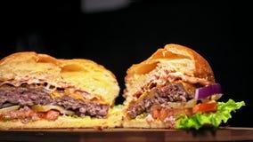 L'hamburger sta cucinando su fondo nero nei guanti neri dell'alimento Panino molto splendido dell'aria e manzo marmorizzato Risto archivi video
