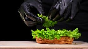 L'hamburger sta cucinando su fondo nero nei guanti neri dell'alimento Panino molto splendido dell'aria e manzo marmorizzato Risto stock footage