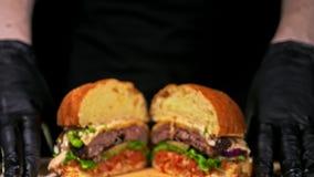 L'hamburger sta cucinando su fondo nero nei guanti neri dell'alimento Panino molto splendido dell'aria e manzo marmorizzato Risto video d archivio