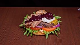 L'hamburger sta cucinando su fondo nero Panino molto splendido dell'aria e manzo marmorizzato Ristorante in cui ogni gli hamburge archivi video