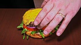 L'hamburger sta cucinando su fondo nero Panino molto splendido dell'aria e manzo marmorizzato Ristorante in cui ogni gli hamburge video d archivio